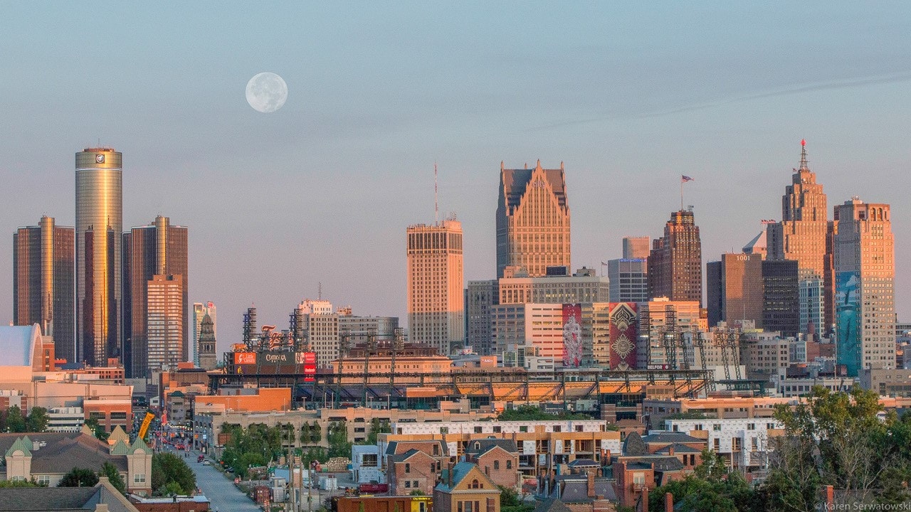 Detroit skyline at dusk with a full moon.
